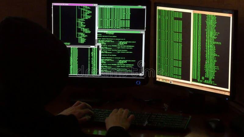 Hacker breaking code. Criminal hacker with black hood royalty free stock photography