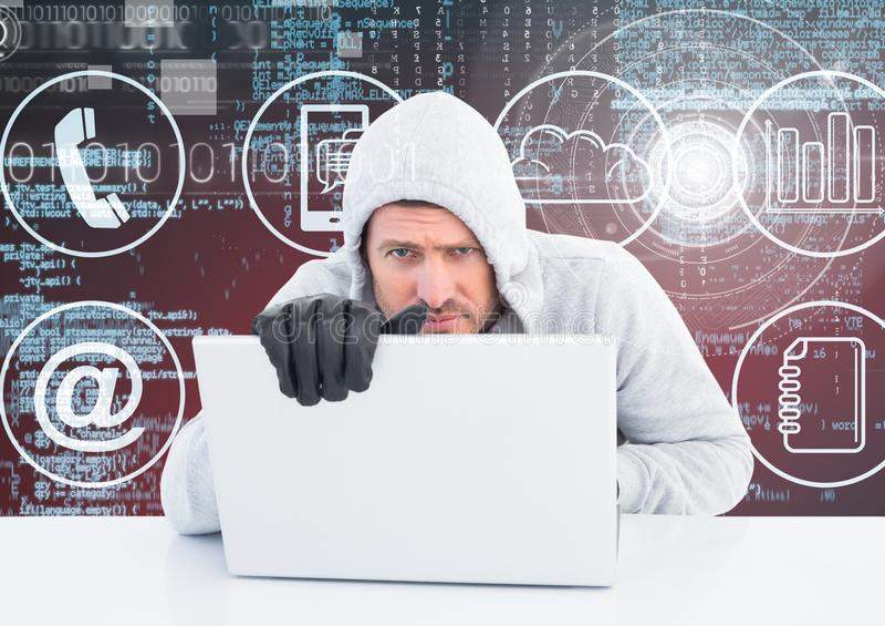 Hacker com luvas usando um portátil na frente do fundo digital fotografia de stock