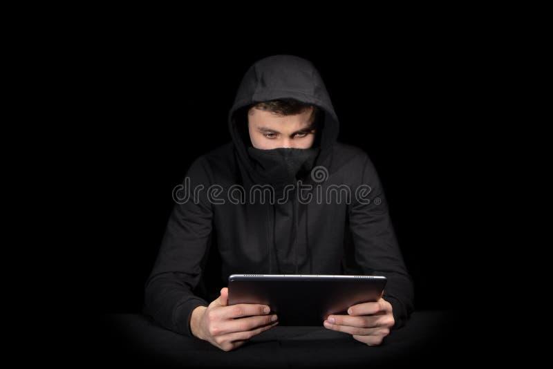 Hacker com o PC da tabuleta que inicia o ataque do cyber, no preto imagem de stock