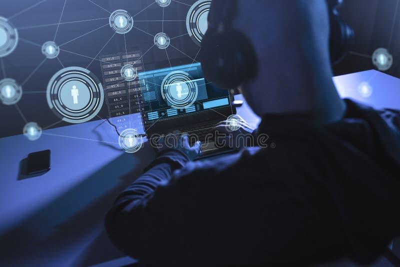 Hacker com rede usando o laptop foto de stock