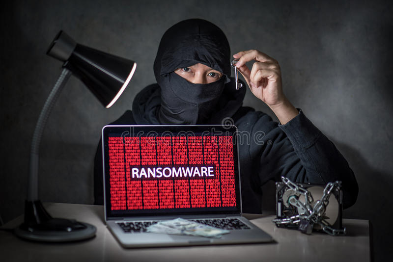 Hacker with computer screen showing ransomware attacking. Hacker holding the key with laptop computer screen showing ransomware attacking, alert in red digital royalty free stock photos