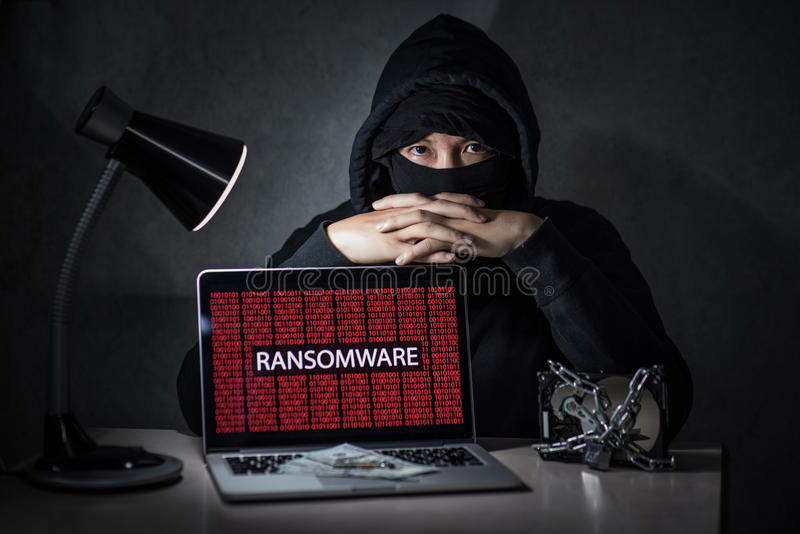 Hacker with computer screen showing ransomware attacking. Hacker with laptop computer screen showing ransomware attacking, alert in red digital binary background royalty free stock images