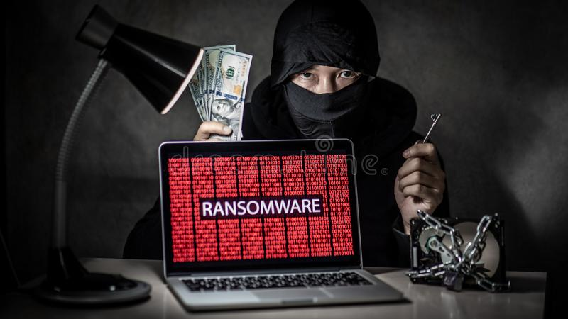 Hacker with computer screen showing ransomware attacking. Male hacker holding key and dollar banknote with laptop computer screen showing red binary ransomware stock image