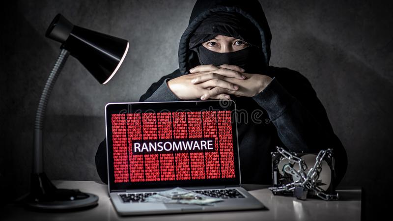 Hacker with computer screen showing ransomware attacking. Male hacker with laptop computer screen showing ransomware attacking, alert in red digital binary stock photos
