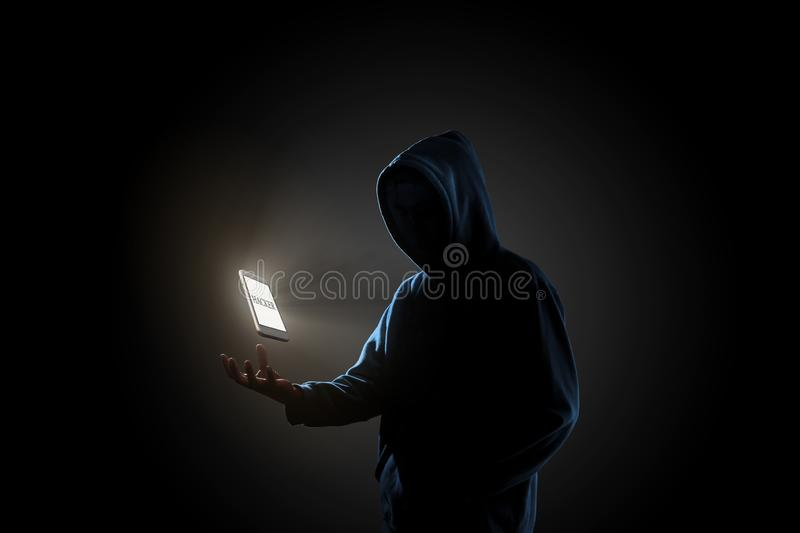 Hacker in dark background concept. White smartphone with text `HACKER` on screen floating above of hacker`s hand in dark background. Finance, business, e stock photo