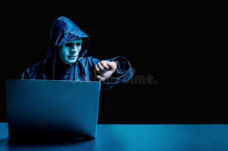 Hacker de computador anônimo na máscara e no hoodie brancos Cara escura obscurecida usando o laptop para o ataque do cyber e veri fotos de stock royalty free