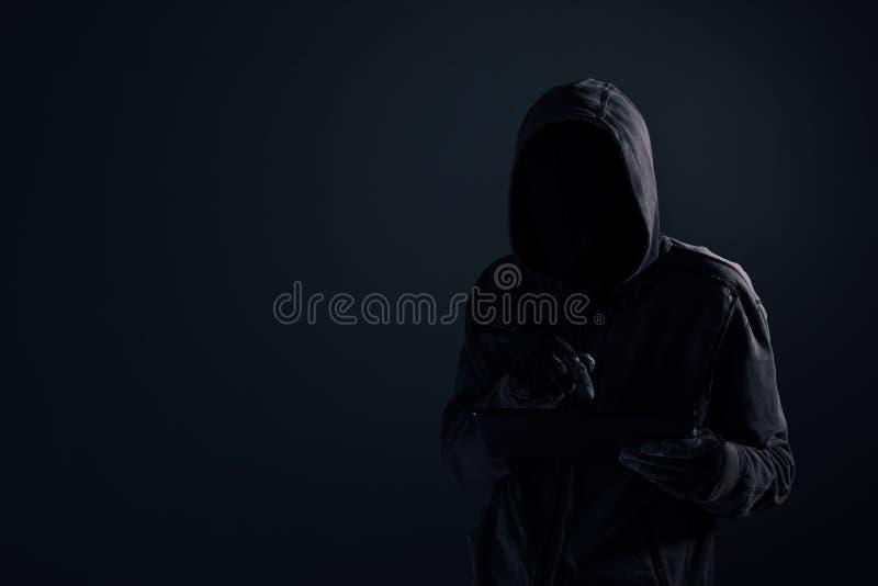 Hacker de computador encapuçado com cara obscurecida usando a tabuleta digital fotos de stock royalty free