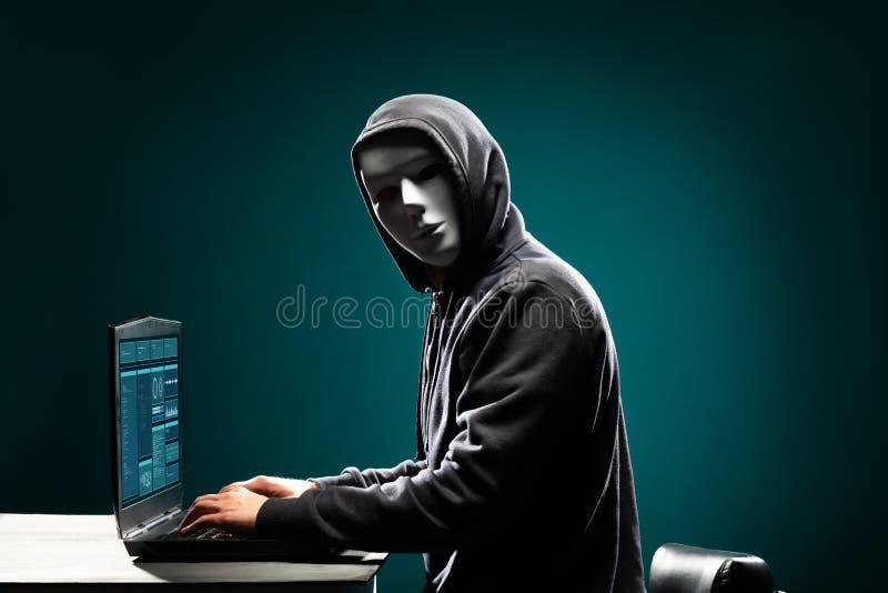 Hacker de computador na máscara e no hoodie brancos Cara escura obscurecida Ladrão dos dados, fraude do Internet, darknet e segur fotos de stock