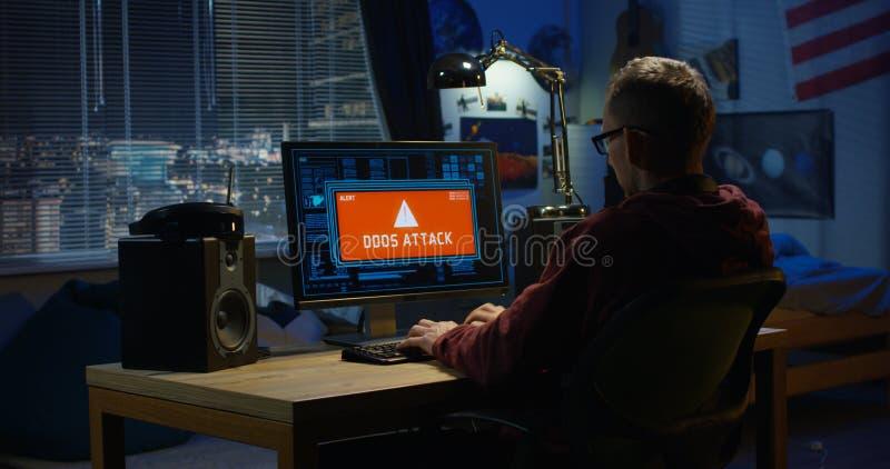Hacker de computador que usa seu computador imagem de stock