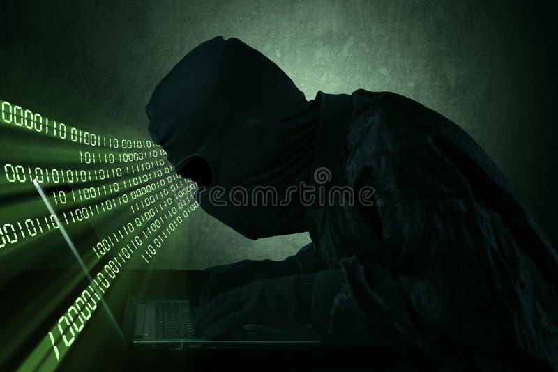 Hacker, der auf einem Laptop schreibt stockbilder