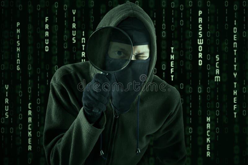 Hacker, der Lupe verwendet lizenzfreies stockfoto