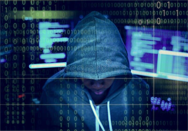 Hacker in einem Kapuzenpulli mit Computerhintergrund lizenzfreies stockfoto
