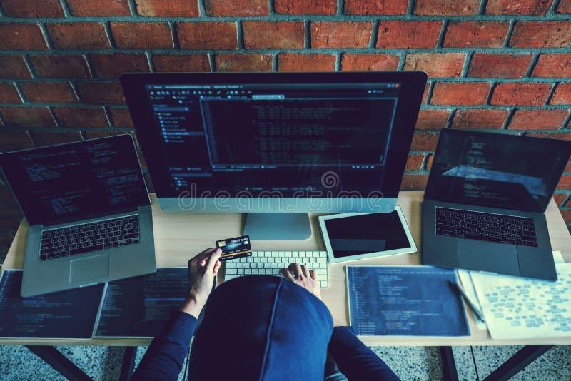 Hacker encapuçado perigoso que usa o cartão de crédito que datilografa dados maus no sistema on-line do computador e que espalha  imagem de stock royalty free