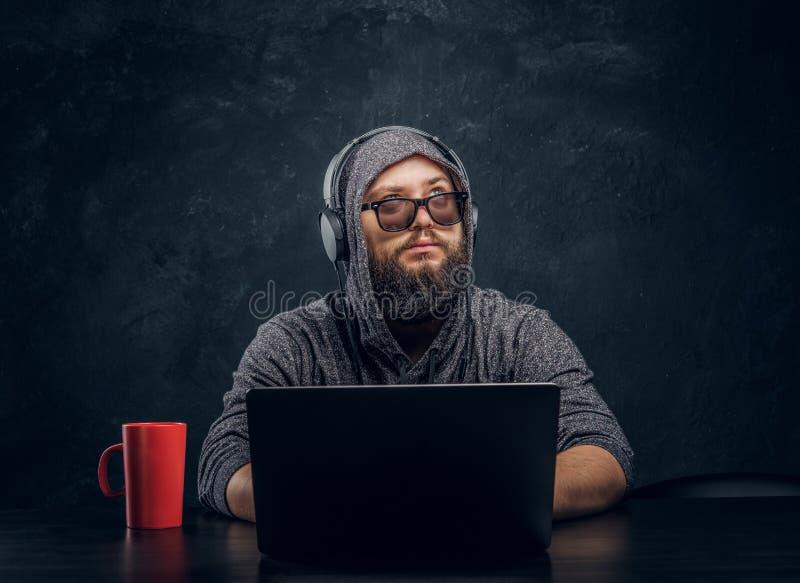 Hacker farpado em um chapéu com óculos de sol e com os fones de ouvido que sentam-se atrás de uma tabela preta foto de stock