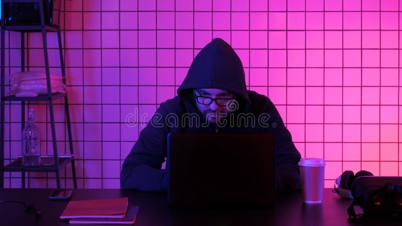 Hacker financeiro masculino novo no trabalho de assento do escritório no portátil foto de stock royalty free
