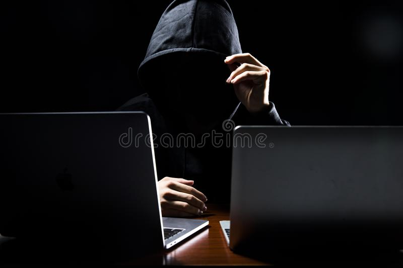 Hacker in front of his computer. Dark face. For security system stock image