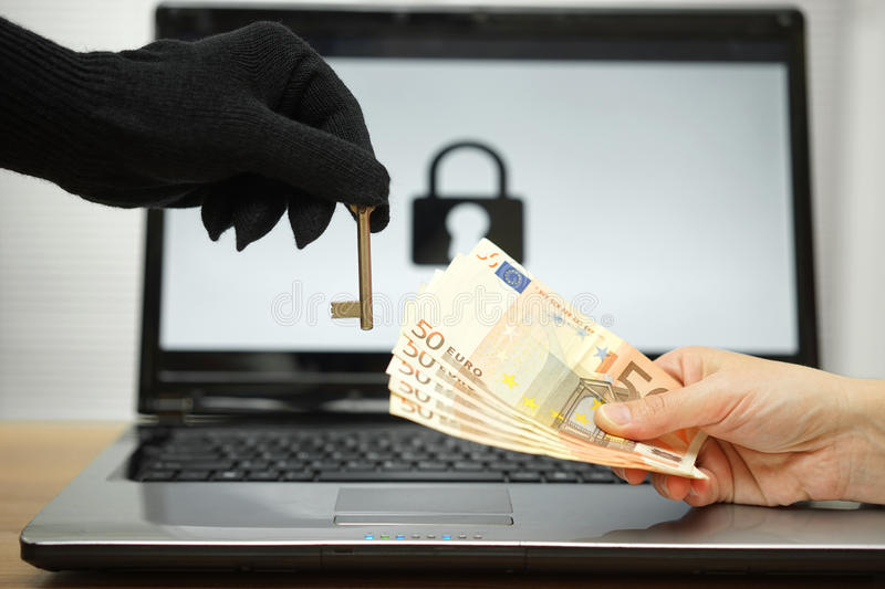 Hacker gives key to victim to restore the personal data on laptop computer.  stock photography