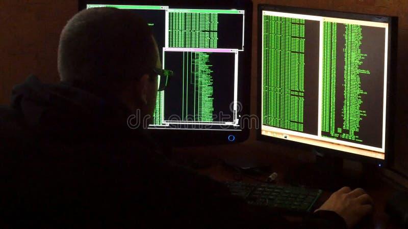 Hacker in glasses breaking code. Criminal hacker penetrating network system from his dark hacker room. Computer program royalty free stock photography