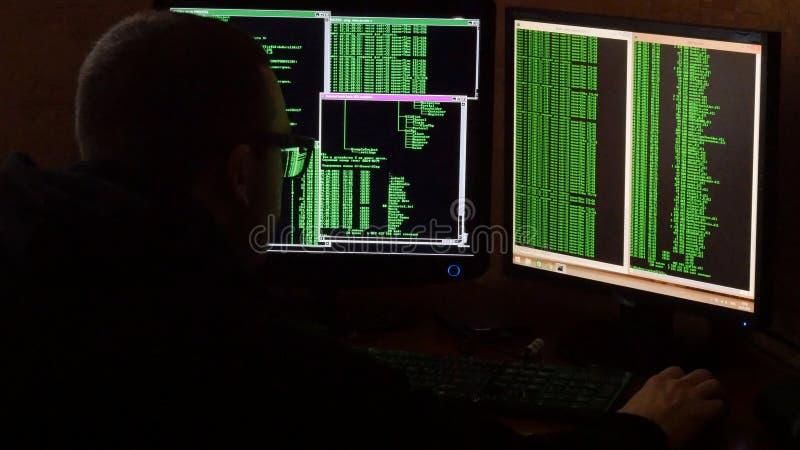 Hacker in glasses breaking code. Criminal hacker penetrating network system from his dark hacker room. Computer program stock image