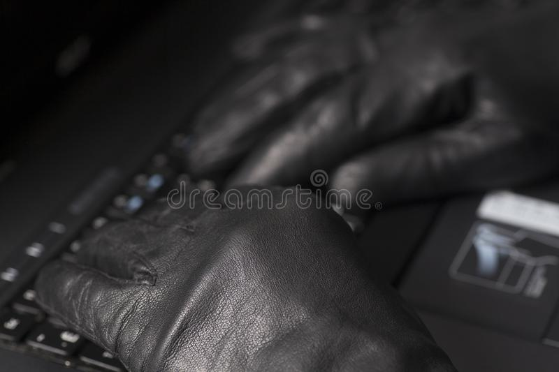 Hacker hand in glove. Working on laptop.Concept of internet criminal hacking stock photography