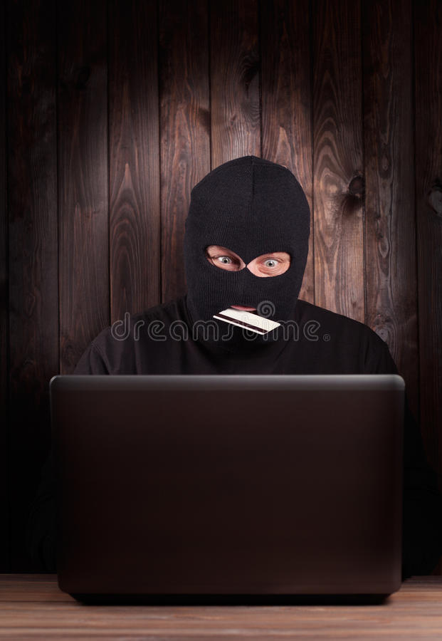 Hacker holding a credit card stock photography