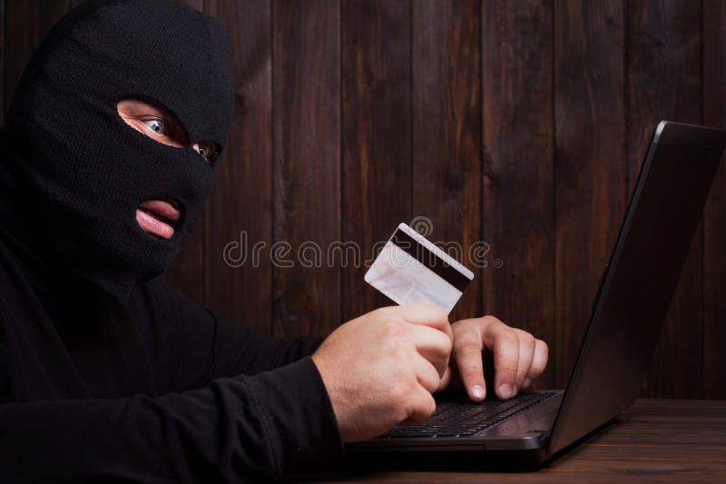 Hacker holding a credit card royalty free stock photography