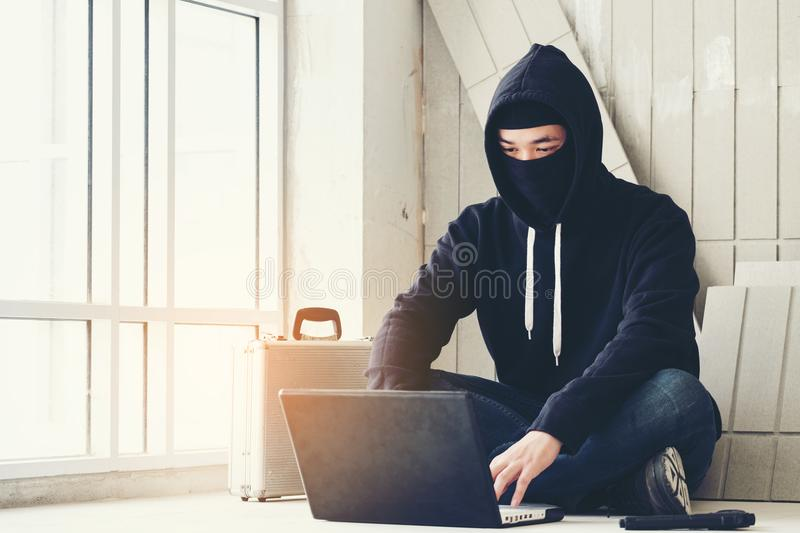 Hacker holding gun working on his computer, war, terrorism , terrorist and bandit concept. Glitch effect and copy space. Black ma. Sked hacker in the black long royalty free stock images