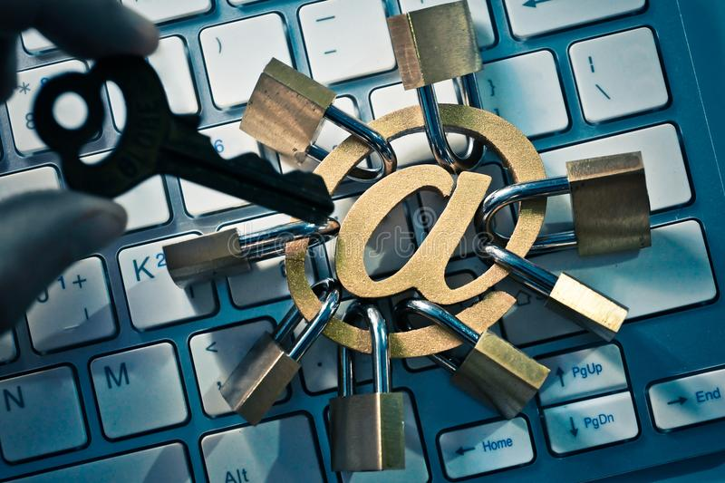Hacker holding a key trying to hack email sign with many padlocks. / Email encryption security and countermeasure concept stock photo