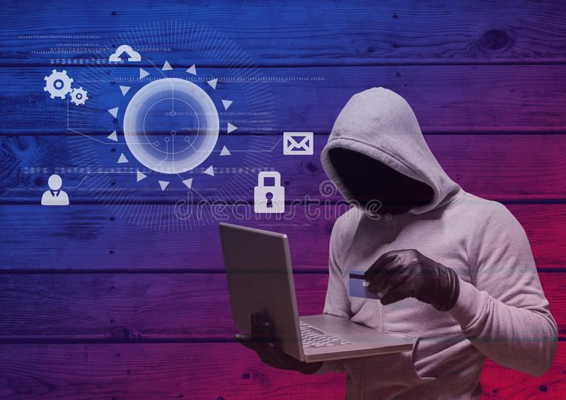Hacker with hood holding a credit card and using a laptop in frond of wood background with digital i royalty free stock images
