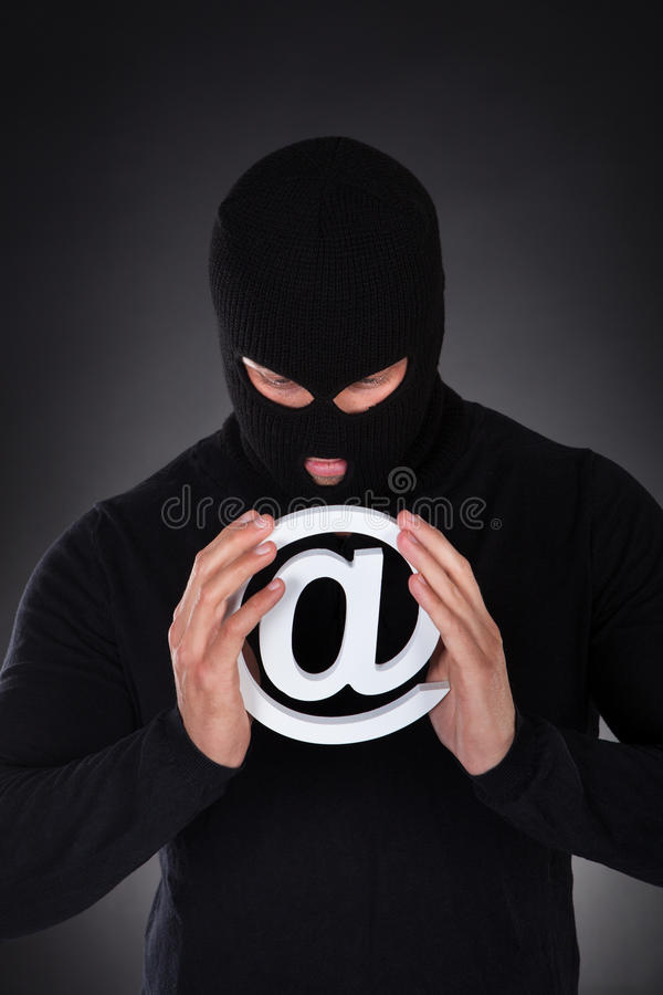 Hacker with an internet domain symbol. Hacker dressed in black wearing a balaclava with a white internet domain symbol stock photos