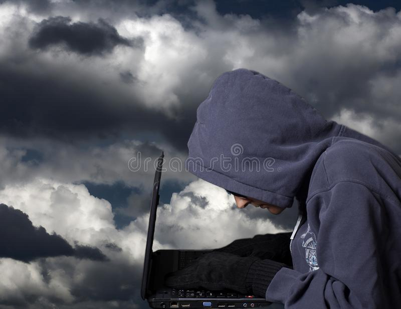 Hacker with laptop .Concept of internet criminal hacking. Hacker with laptop on dramatic sky .Concept of internet criminal hacking royalty free stock image