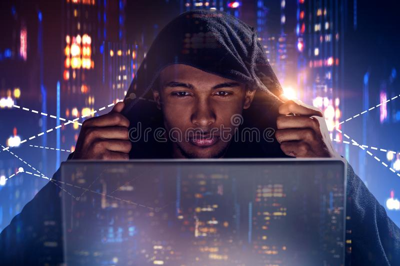 Hacker with laptop in night city, graphs. African American man in black hoodie looking at laptop screen in night city. Graphs hologram behind him. Security royalty free stock images