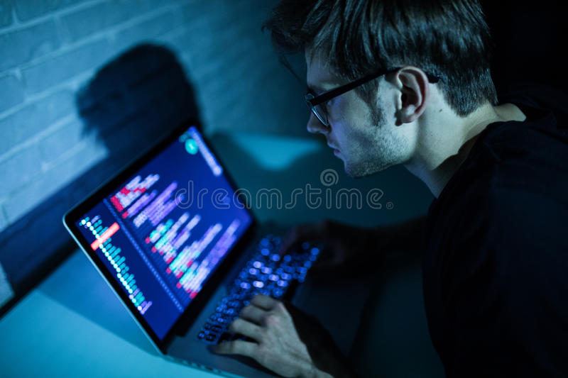 Hacker man trying to breach security of a computer system search internet. Hacker royalty free stock photo