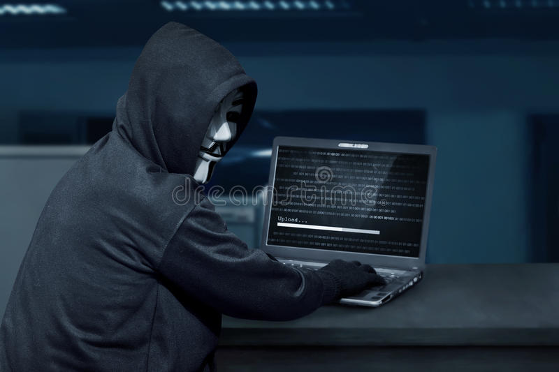 Hacker man wearing mask using laptop to upload computer virus. In the office royalty free stock images