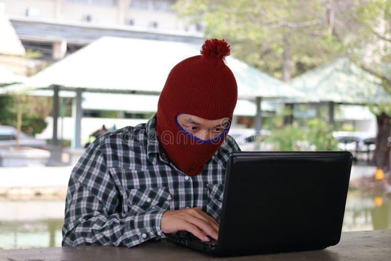 Hacker mascarado em um passa-montanhas que senta-se em uma mesa que rouba a informação com portátil Conceito do criminoso de comp fotos de stock