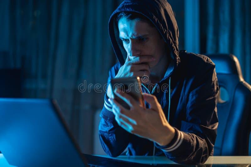 Hacker masculino na capa que guarda o telefone em suas m?os que tentam roubar bancos de dados do acesso com senhas CyberSecurity fotografia de stock royalty free