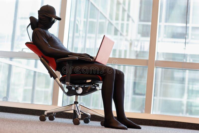 Hacker anônimo que trabalha com o portátil no escritório foto de stock royalty free