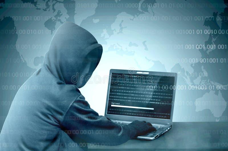 Hacker no hoodie preto usando o portátil na mesa a cortar o sistema com código binário e para transferir arquivos pela rede o mal imagens de stock