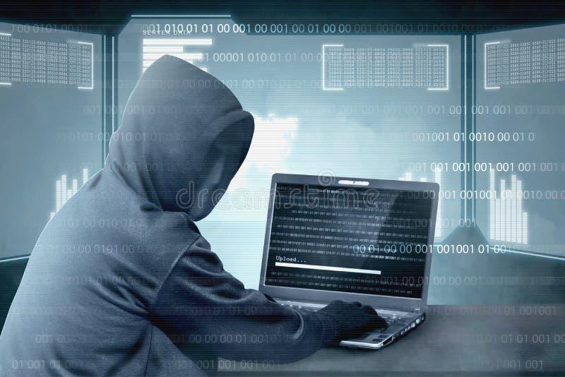 Hacker no hoodie preto usando o portátil na mesa a cortar o sistema com código binário e para transferir arquivos pela rede o mal fotos de stock
