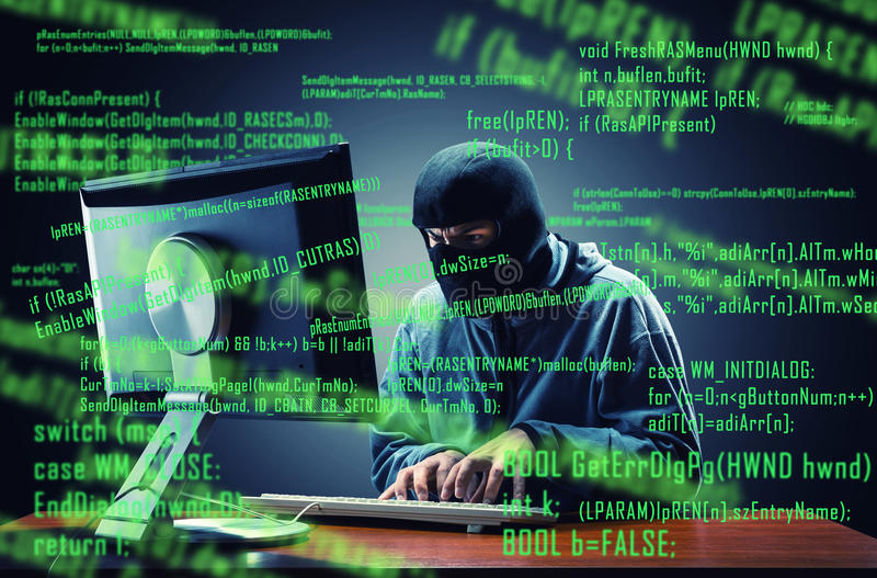 Hacker in the office. Hacker in mask stealing information in the office stock photography