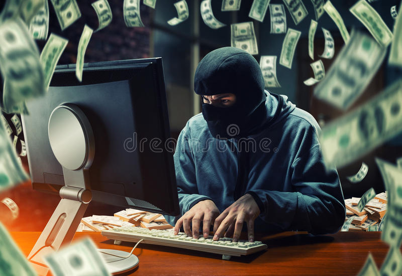 Hacker in the office. Hacker in mask stealing information and money in the office royalty free stock photo