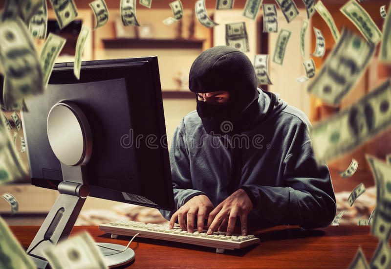 Hacker in the office. Hacker in mask stealing information and money at home royalty free stock photography