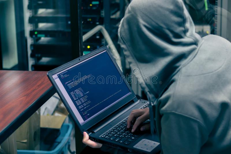Hacker Organizes Massive Data Breach Attack on Corporate Servers. He is in Secret Location. Their Hideout is Dark, Neon Lit,Server room stock photos