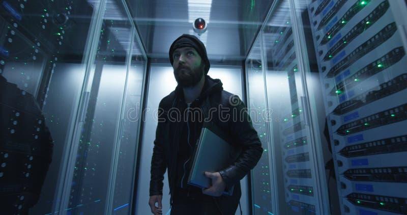 Hacker que sneaking com as fileiras dos servidores com portátil fotografia de stock royalty free