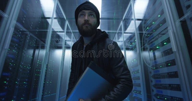 Hacker que sneaking com as fileiras dos servidores com portátil imagem de stock royalty free