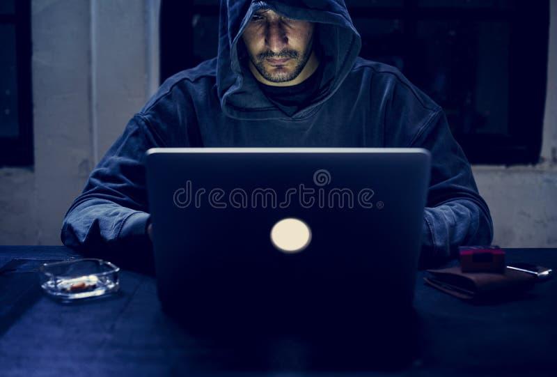 Hacker que trabalha no crime do cyber do computador imagem de stock