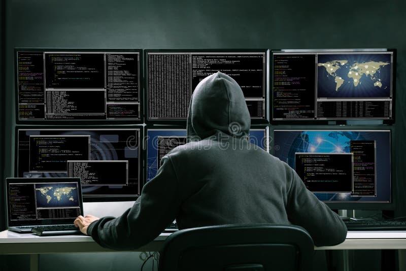 Hacker que usa computadores múltiplos para roubar dados foto de stock