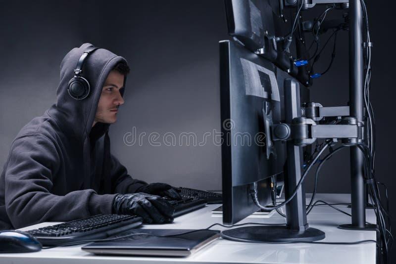 Hacker que usa computadores múltiplos para roubar dados imagens de stock