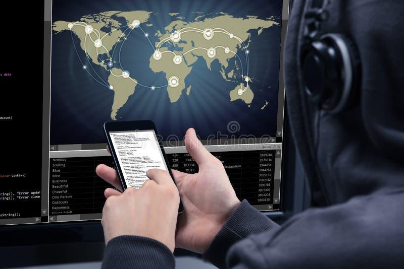 Hacker que usa o telefone celular para roubar dados do computador imagem de stock