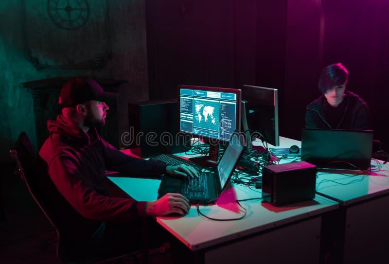 Hacker ricercati che codificano virus Ransomware utilizzando computer e laptop nello scantinato Attacco cibernetico, rottura del  fotografie stock libere da diritti